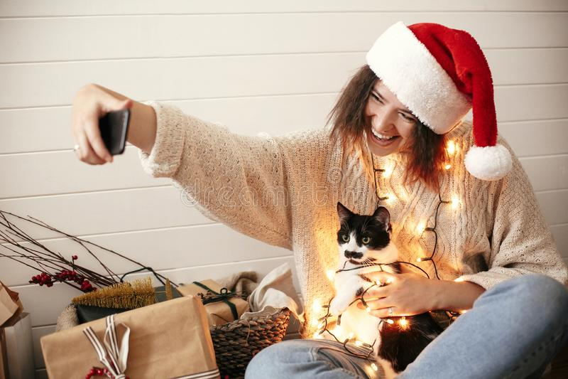 Stylish happy girl in santa hat taking selfie with cute cat in christmas lights on background of gifts. Young hipster woman in. Sweater hugging kitty with funny stock photography