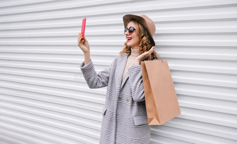 Stylish happy laughing woman taking selfie picture by smartphone with shopping bag in gray coat, round hat posing on city stock images