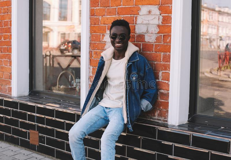 Stylish happy smiling african man wearing jeans jacket sitting on city street over brick wall. Background stock photos