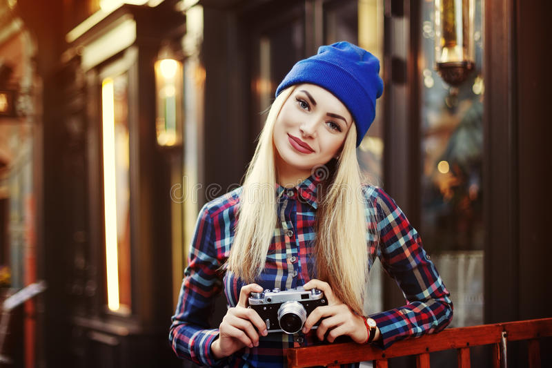 Stylish happy smiling hipster girl with retro vintage camera. Close up street portrait. Toned royalty free stock photography