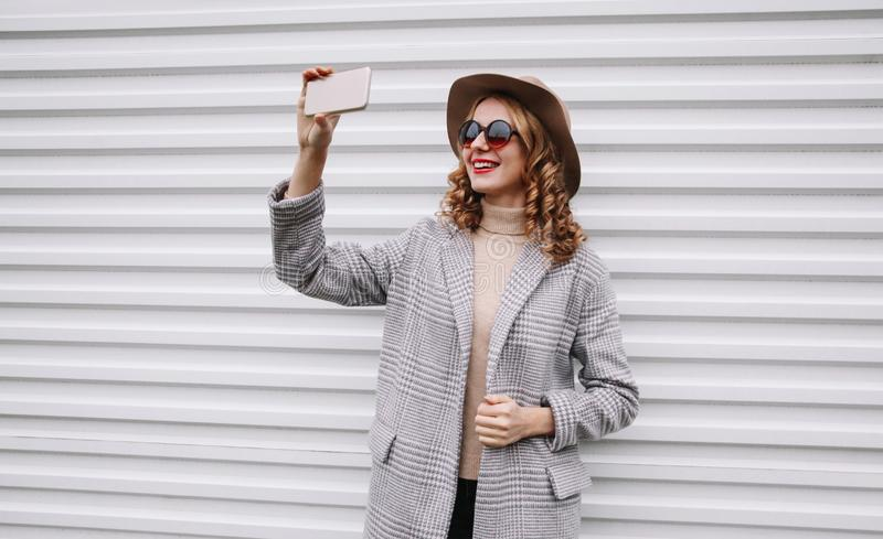 Stylish happy smiling woman taking selfie picture by smartphone in gray coat, round hat posing over white wall royalty free stock photography