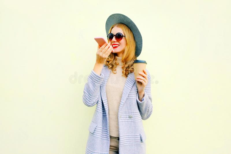 Stylish happy smiling young woman with smartphone using voice command recorder or calling, wearing coat jacket, round hat. On wall background royalty free stock photography