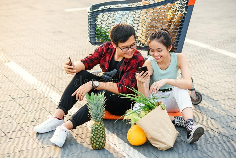 Attractive smiling 30s couple relaxing after shopping,sitting on the ground near big store and watching amusing pictures stock photography