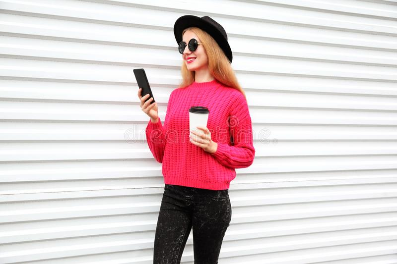 Stylish happy woman looking at phone holding coffee cup, female model wearing black round hat, pink knitted sweater in city stock photos