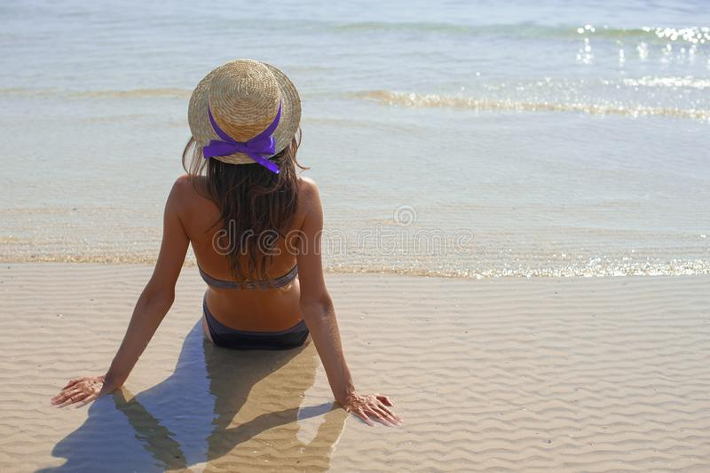 Stylish happy young woman relaxing on beach. girl sitting and tanning on beach near sea with waves, sunny warm weather. Summer royalty free stock image