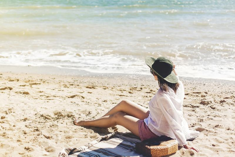 Stylish happy young woman relaxing on beach. Hipster girl in white shirt and hat sitting and tanning on beach near sea with waves. Sunny warm weather. Summer royalty free stock photography