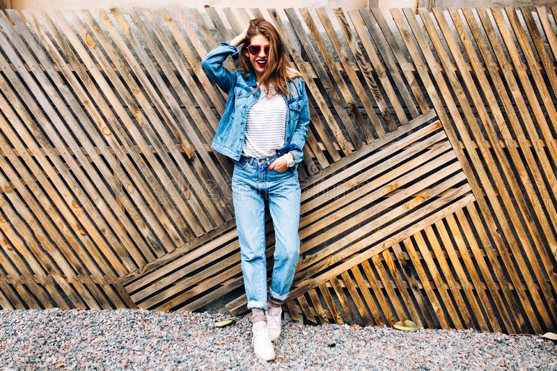 Stylish happy young woman wearing boyfrend jeans and white sneakers with hand in pocket. Full-length portrait of smiling royalty free stock photography