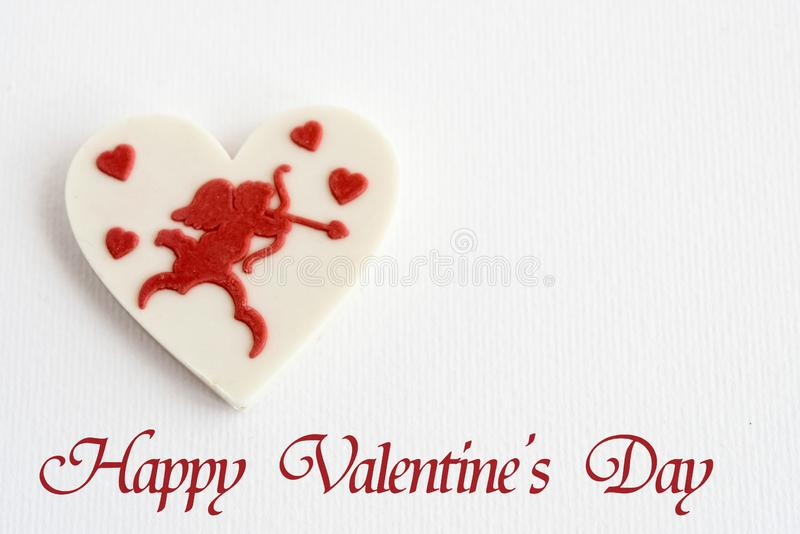 stylish heart candy with cupid on white background, happy valentines day text, greeting card concept stock images