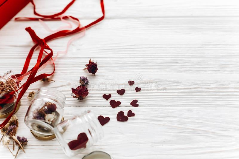stylish hearts in glass jar and roses and ribbons on white wooden background. unusual happy valentines day concept. greeting card stock photos