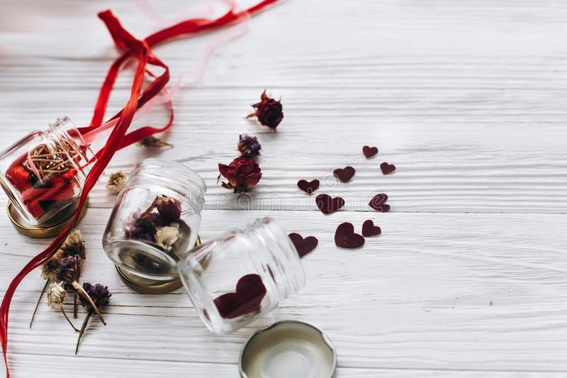 stylish hearts in glass jar and roses and ribbons on white wooden background. unusual happy valentines day concept. greeting card royalty free stock images