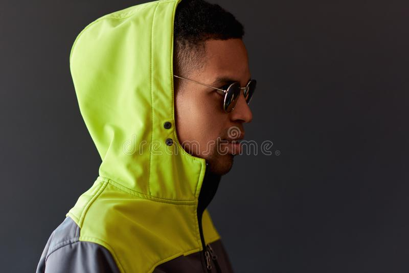 Stylish hipster African American man looking through mirror sunglasses, wearing green sport hoody, posing on black studio wall. royalty free stock image