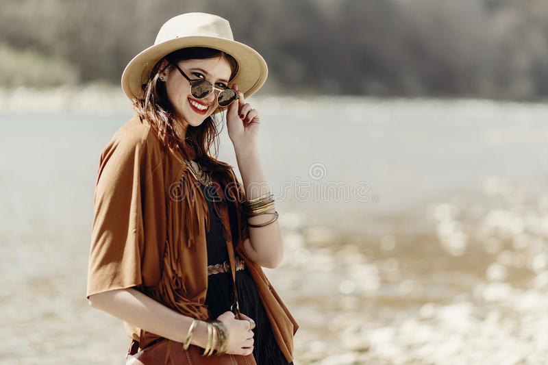 stylish hipster boho woman smiling in sunglasses with hat, leather bag, fringe poncho and accessory. happy traveler girl look, ne royalty free stock image