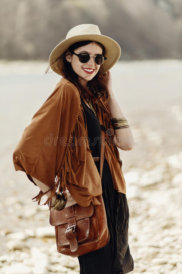 Stylish hipster boho woman smiling in sunglasses with hat, leather bag, fringe poncho and accessory. traveler girl look, near. Beach in mountains. atmospheric royalty free stock photography