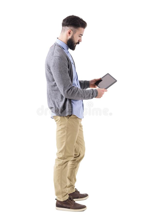 Stylish hipster businessman holding and watching tablet pad computer. Side view. royalty free stock photo