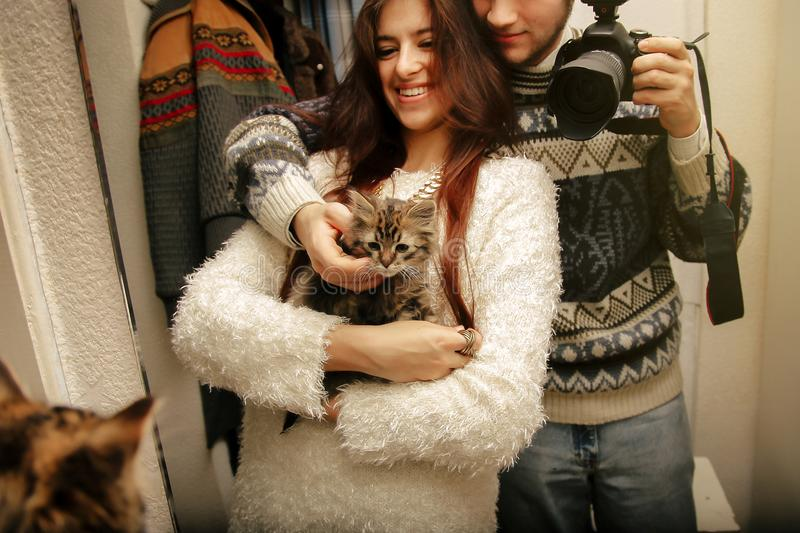 Stylish hipster couple adopted homeless sweet little kitten and royalty free stock image