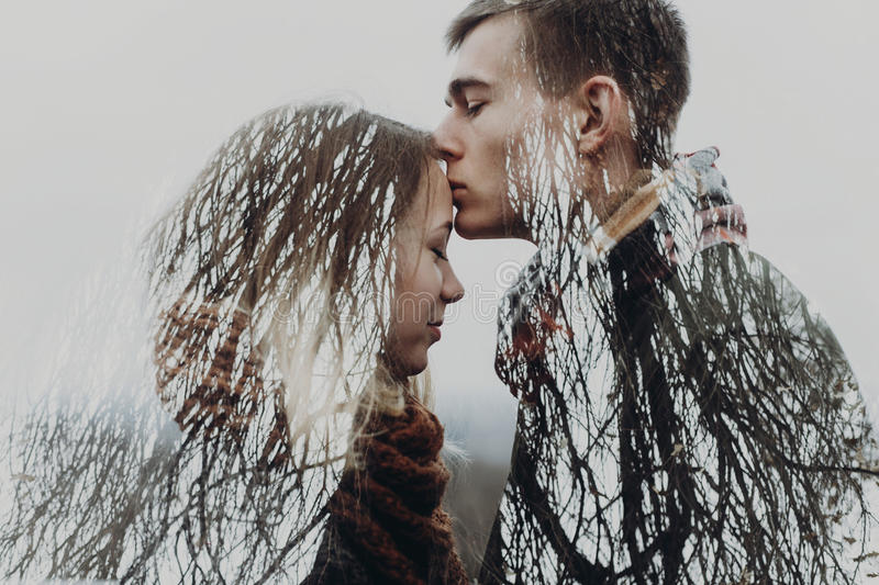 Stylish hipster couple in double exposure with tree branches in stock photo