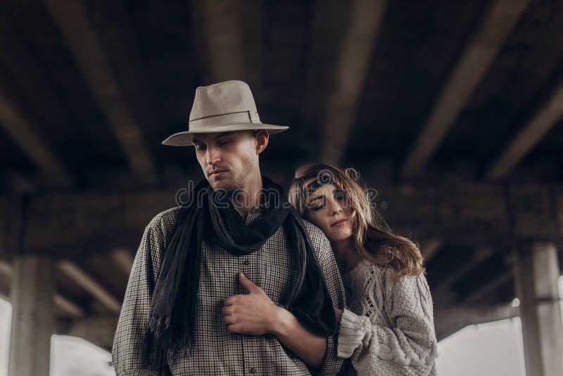 Stylish hipster couple dreaming under abandoned bridge. boho gyp stock images