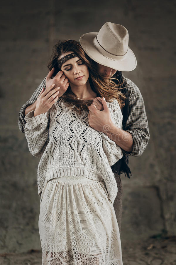 stylish hipster couple gently hugging. man in hat sensual touching boho woman in knitted sweater. atmospheric sensual moment. royalty free stock images