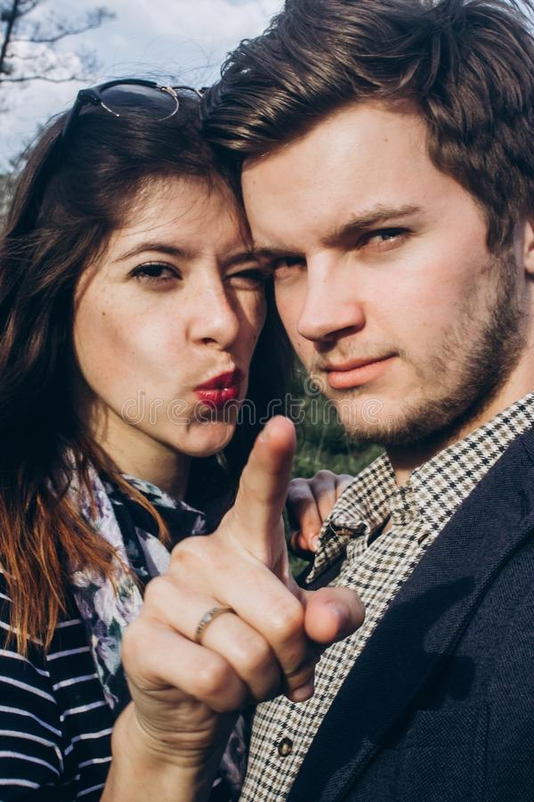 Stylish hipster couple having fun and smiling in sunny countryside. space for text. rustic man and woman pointing forward, funny. Stylish hipster couple having royalty free stock photography