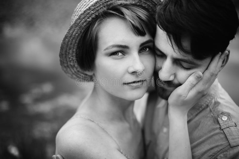 stylish hipster couple hugging at lake. man and woman embracing, in love relaxing in summer park, picnic date. girl in royalty free stock images