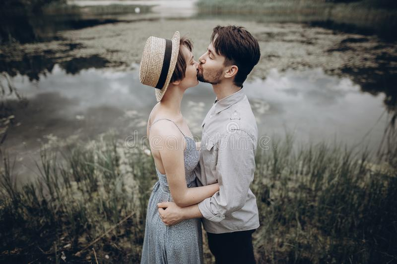 Stylish hipster couple hugging at lake. man and woman in modern royalty free stock photography