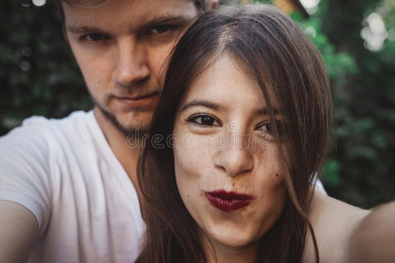 Stylish hipster couple making selfie and embracing. Happy family couple in love making self portrait and smiling in evening summer. City. Vacation and travel stock images