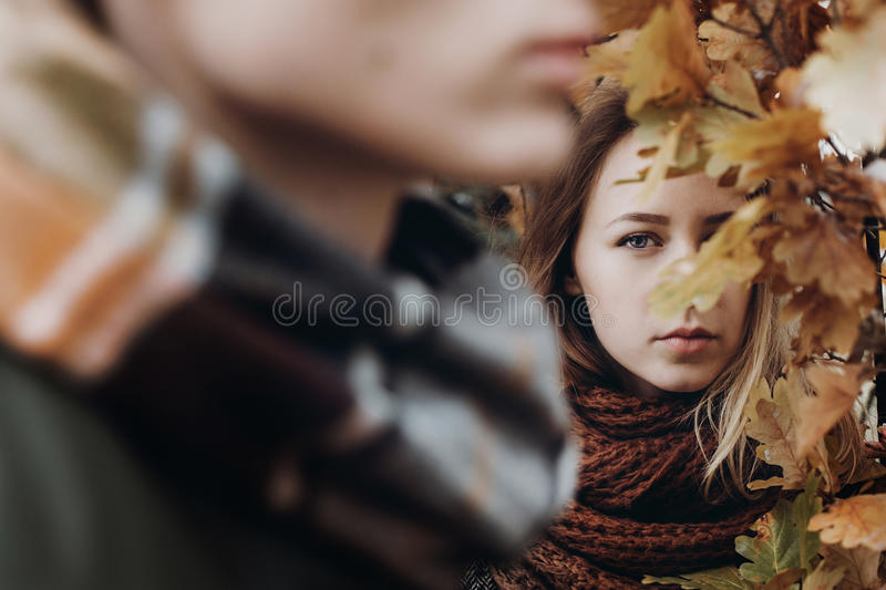 Stylish hipster couple posing and looking under yellow leaves in royalty free stock photography