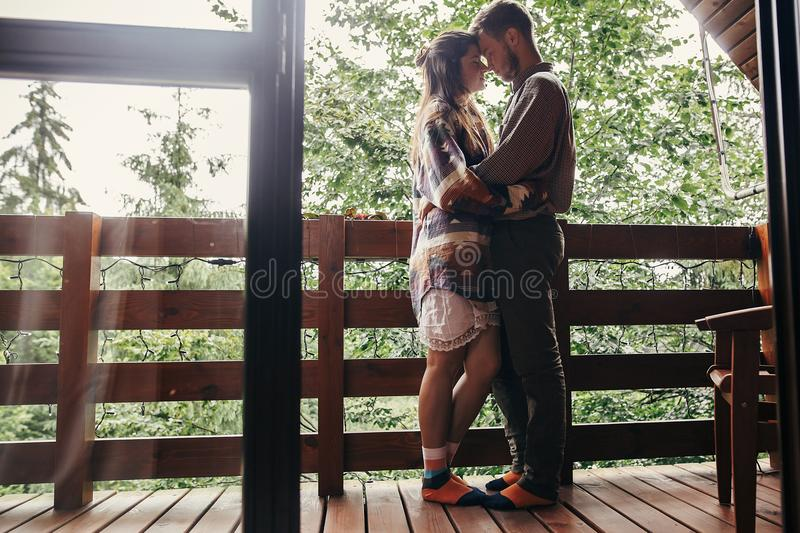 Stylish hipster couple relaxing on porch, hugging in wooden cottage at woods in mountains. happy family embracing at home. summer. Vacation. atmospheric moment royalty free stock photo