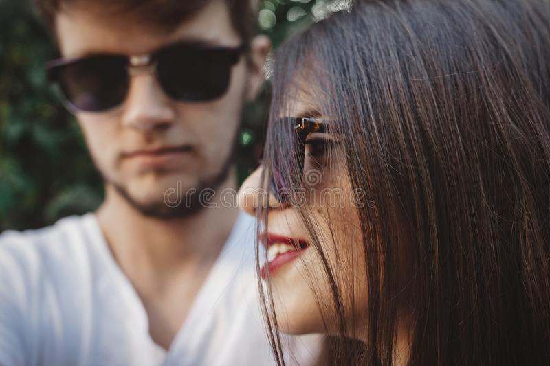 Stylish hipster couple in sunglasses posing and making cool selfie. Happy family couple in love making self portrait and embracing. In evening summer city stock photo