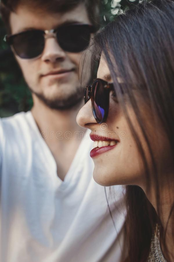 Stylish hipster couple in sunglasses smiling and making cool selfie. Happy family couple in love making self portrait and laughing. In evening summer city royalty free stock photos