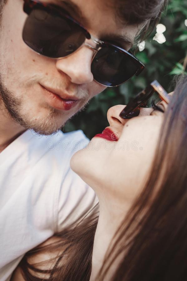 Stylish hipster couple in sunglasses smiling and making cool selfie. Happy family couple in love making self portrait and kissing. In evening summer city royalty free stock photo