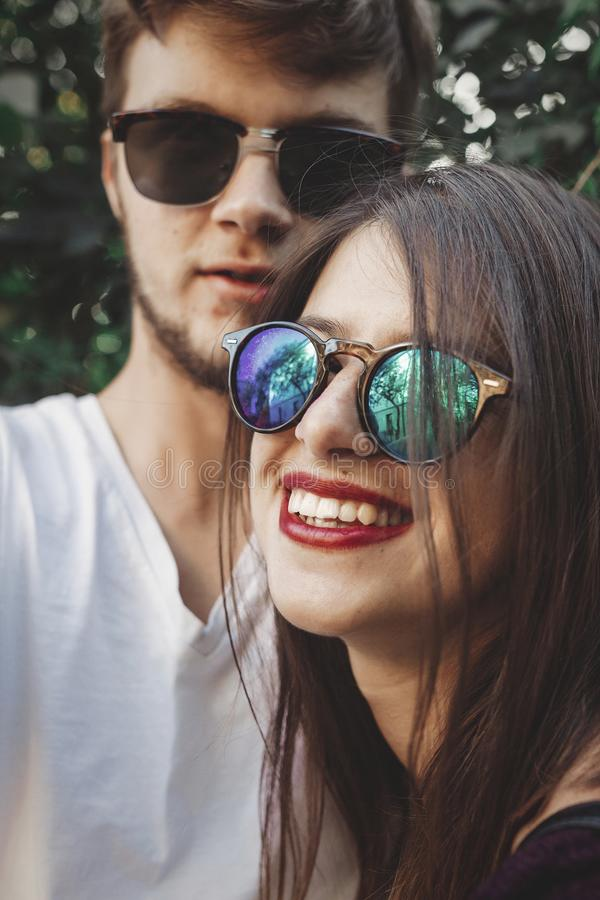 Stylish hipster couple in sunglasses smiling and making cool selfie. Happy family couple in love making self portrait and laughing. In evening summer city royalty free stock photography