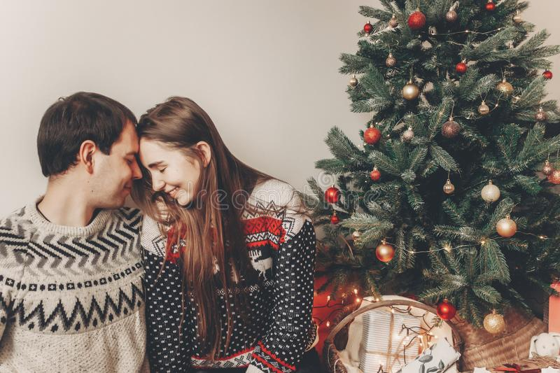 stylish hipster couple in sweaters hugging and embracing at christmas tree in cozy evening room. atmospheric moments. merry chris royalty free stock photos