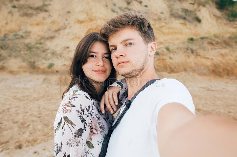 Stylish hipster couple taking selfie on beach at sandy cliff at sea. Summer vacation. Portrait of happy young family on honeymoon. On tropical island making stock image