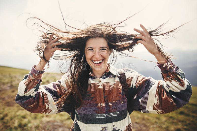 Stylish hipster girl with backpack and windy hair smiling on top of mountains. Portrait of happy young woman relaxing. Carefree. Mood. Amazing atmospheric royalty free stock photography