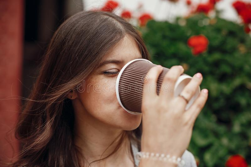 Stylish hipster girl with beautiful hair drinking coffee from c royalty free stock images