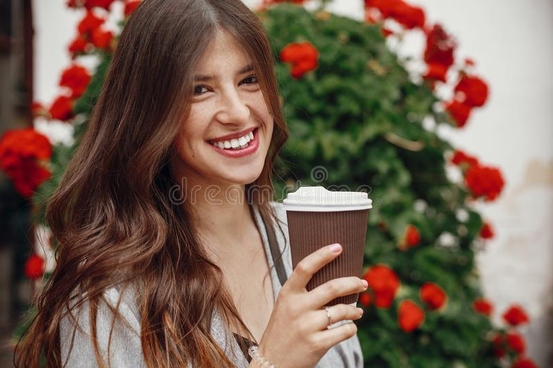Stylish hipster girl with beautiful hair and perfect smile holding coffee cup in city street on background of flowers. Gorgeous stock photos