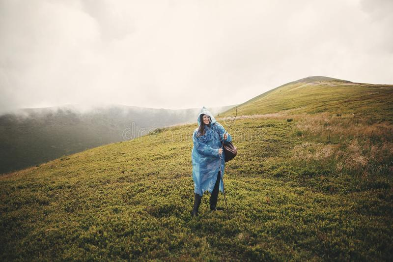 Stylish hipster girl in blue raincoat and with backpack standing on top of misty mountains and clouds. Funny young woman traveler stock photography