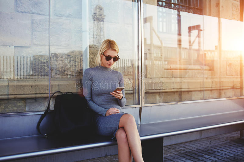 Stylish hipster girl chatting in network via smart phone with her friends while sitting on bus stop in summer day, royalty free stock images