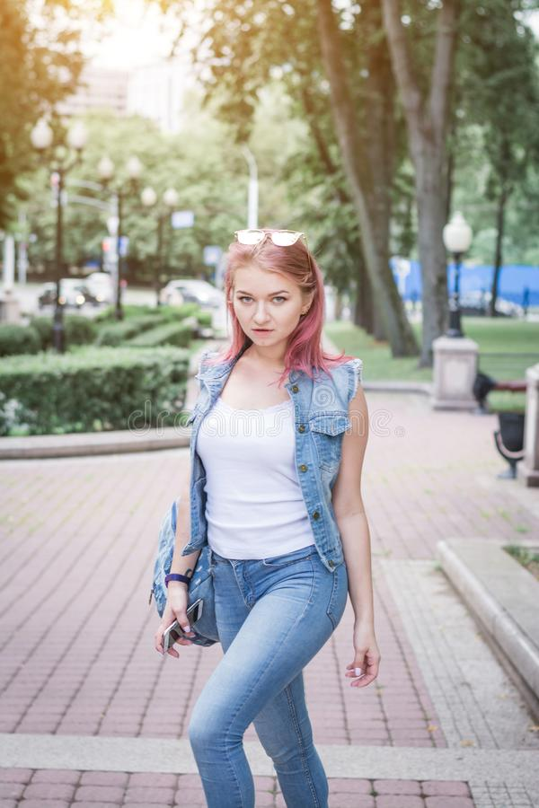 Stylish hipster girl in denim clothes on a city street royalty free stock photography