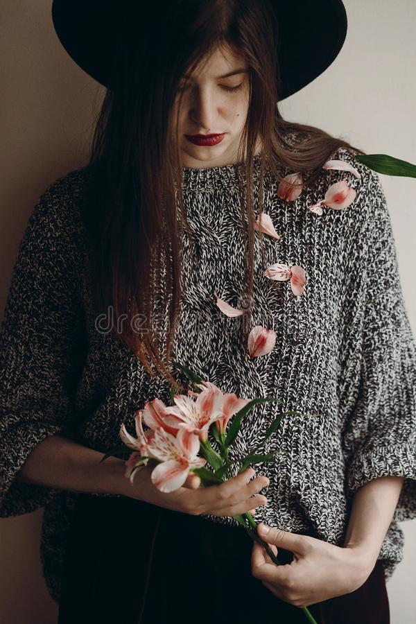 Stylish hipster girl in hat holding pink flowers and petals on s stock photos