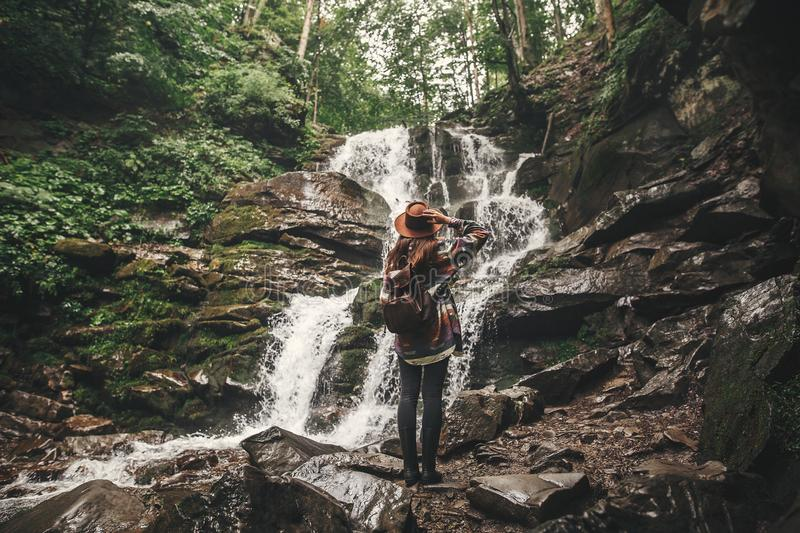 Stylish hipster girl in hat traveling in mountains. Young woman with backpack exploring in summer forest, looking at waterfall. stock photo