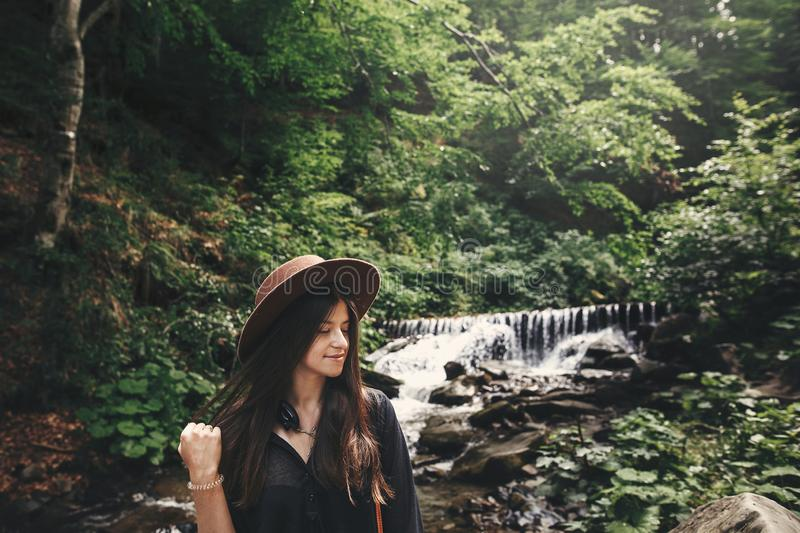Stylish hipster girl in hat traveling in woods. Young woman with beautiful hair exploring in summer forest, looking at river. stock images
