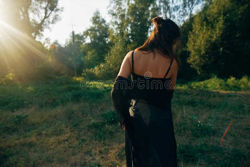 Stylish hipster girl having fun in sunny park in amazing sunbeams, atmospheric moment. Fashionable cool woman dancing in evening. Light, back view. Selective stock photos