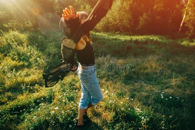 Stylish hipster girl having fun in sunny park in amazing sunbeams, atmospheric moment. Fashionable cool woman dancing in evening. Light. Selective focus. Retro royalty free stock images