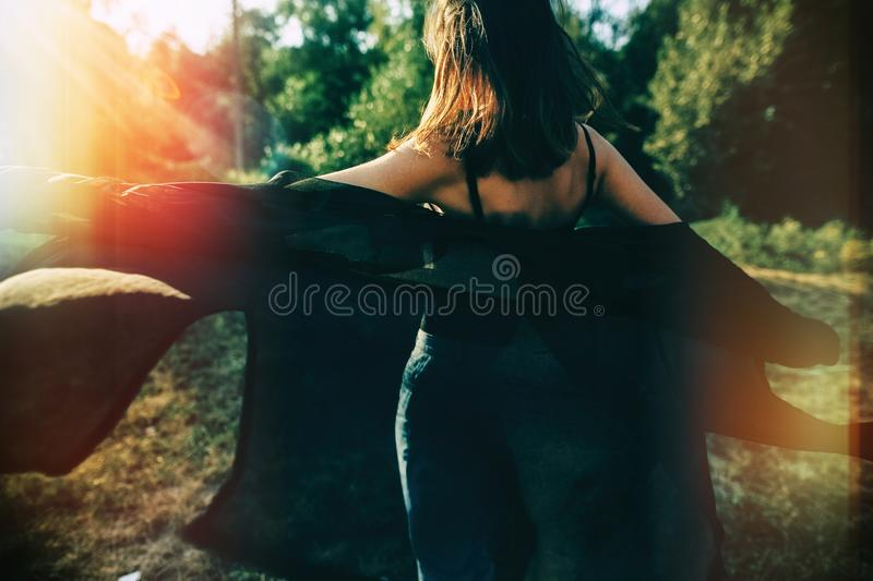 Stylish hipster girl having fun in sunny park in amazing sunbeams, atmospheric moment. Fashionable cool woman dancing in evening. Light, back view. Selective royalty free stock photography