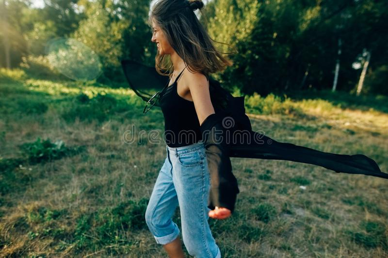 Stylish hipster girl having fun in sunny park in amazing sunbeams, atmospheric moment. Fashionable cool woman dancing in evening. Light. Selective focus. Retro stock image