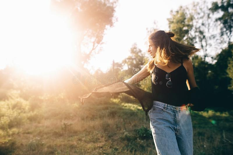 Stylish hipster girl having fun in sunny park in amazing sunbeams, atmospheric moment. Fashionable cool woman dancing in evening. Light. Selective focus. Retro royalty free stock photography