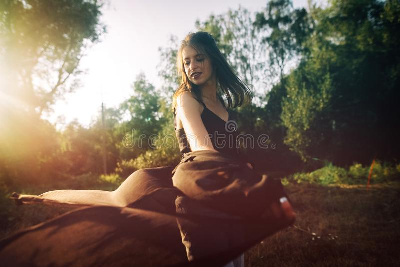 Stylish hipster girl having fun in sunny park in amazing sunbeams, atmospheric moment. Fashionable cool woman dancing and moving. In evening light. Selective royalty free stock photos