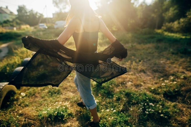 Stylish hipster girl having fun in sunny park in amazing sunbeams, atmospheric moment. Fashionable cool woman dancing and moving. In evening light. Selective royalty free stock photo